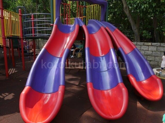 九龍公園の子ども遊具エリアのカラフルなすべり台