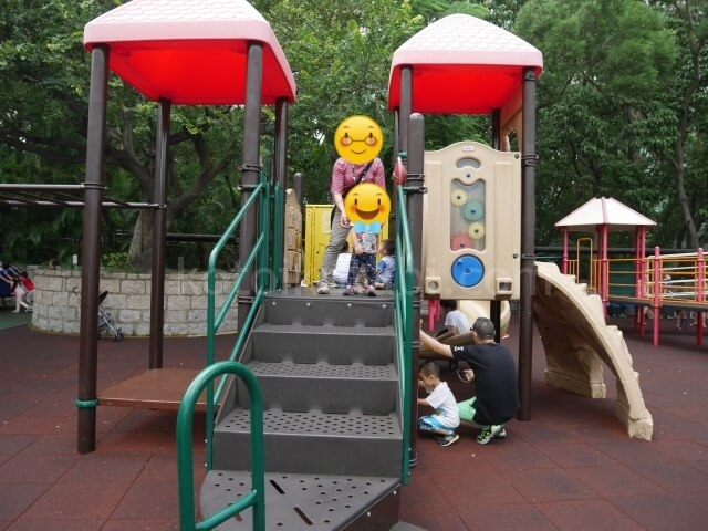 九龍公園の子ども遊具エリアで遊ぶ母と息子